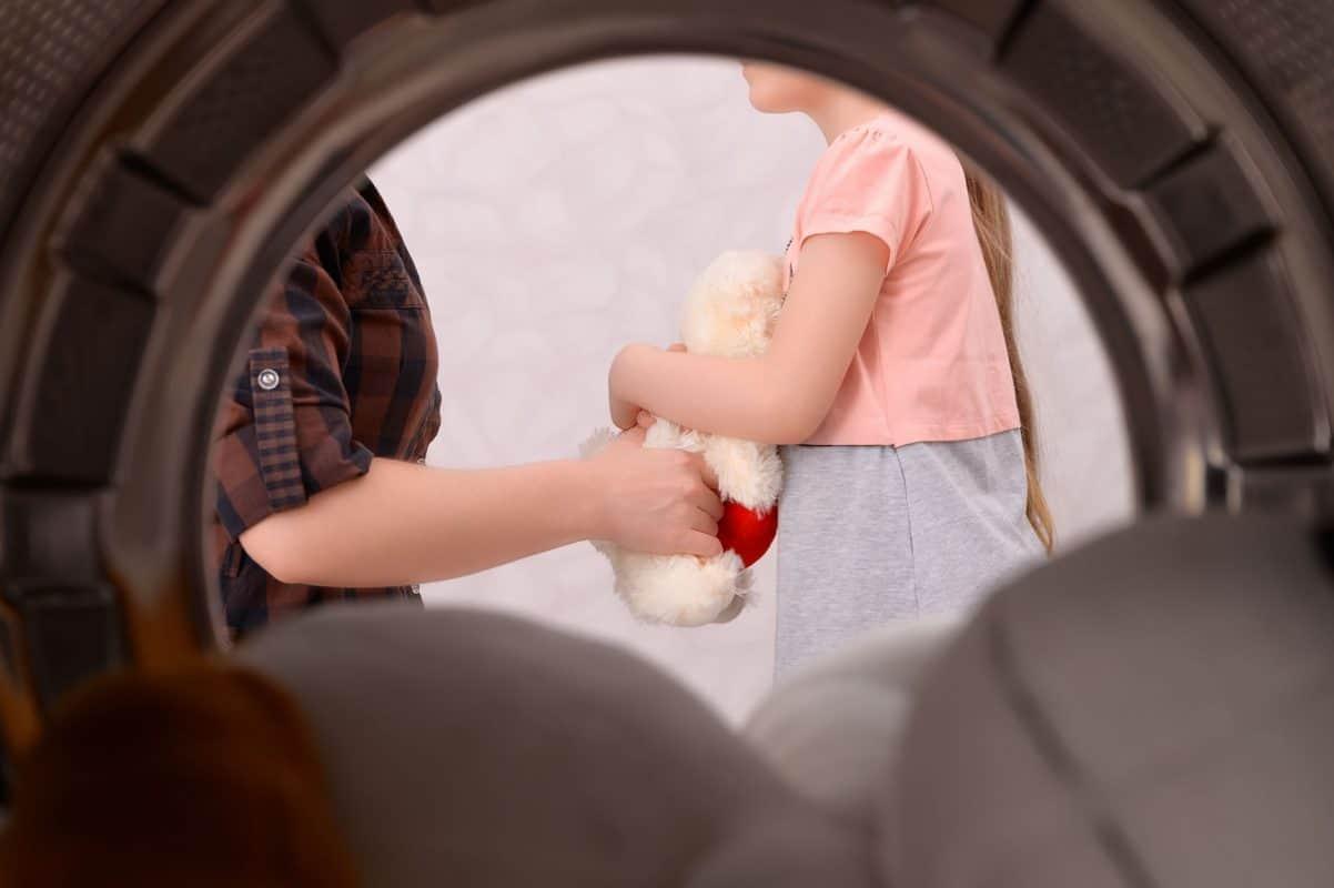 Babyspielzeug reinigen: Blick aus der Waschmaschine heraus auf Mutter und Kind mit Kuscheltier